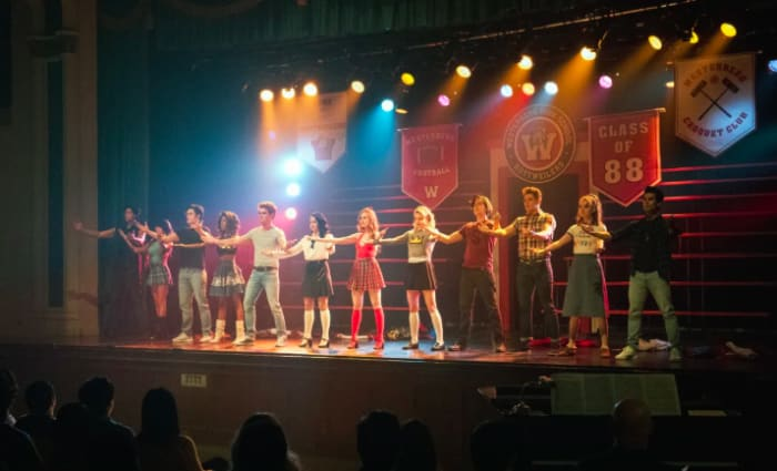 Grupo de estudiantes cantando sobre un escenario en la serie Riverdale