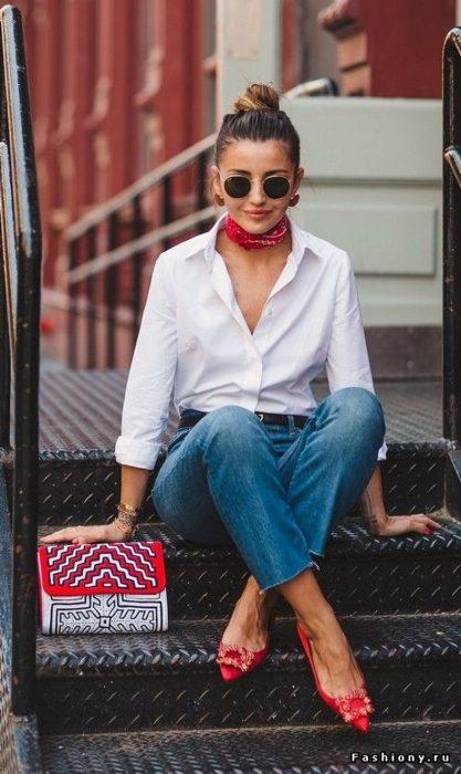 Chica modelando un atuendo de camisa de botones blanca, unos jens de mezclilla y un pañuelo rojo en el cuello