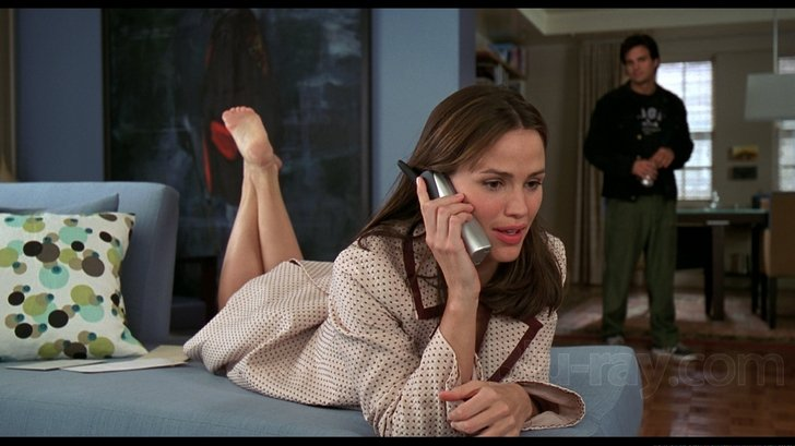 La actriz Jeniffer Garner sobre un sofá y detrás el actor Mark Ruffalo