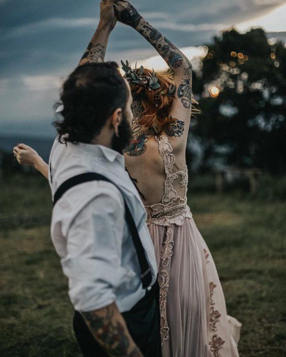 Novios bailando en su boda vikinga, esposa con vestido rosa de encaje sin mangas y tatuajes en los brazos, novio con barba, camisa blanca y tirantes