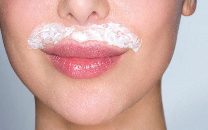 Mujer mostrando sus labios y la decoloración que hace a su bigote femenino