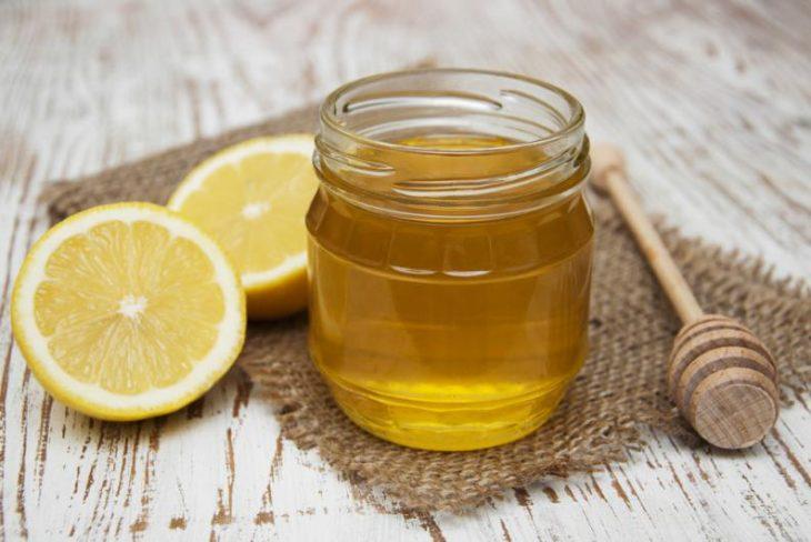 Tarro de miel y rodajas de limón sobre una mesa de madera