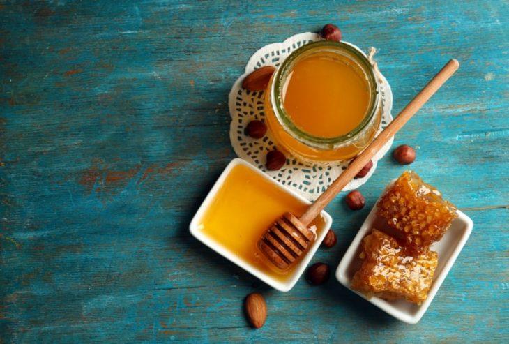 Tarros de miel sobre una mesa de madera de tono azul aqua