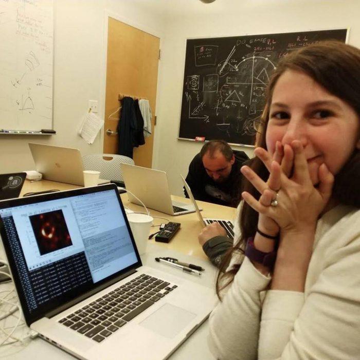 Joven científica, Katie Bouman, emocionada viendo en la computadora la primera fotografía tomada de un agujero negro gracias al algoritmo que desarrolló