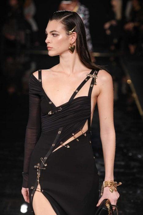 Chica con vestido negro ceñido a su cuerpo con correas y un broche en forma de corazón sobre su cabello