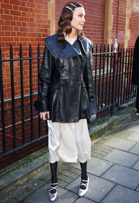Chica en la calle con falda color crema, chamarra de piel negra y un par de broches de perlas