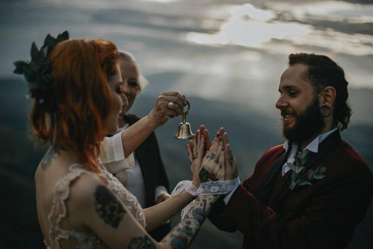 Pareja de prometidos se casa en boda nórdica, esposa con vestido de encaje rosa pálido y esposo con traje rojo vino, tomándose las manos
