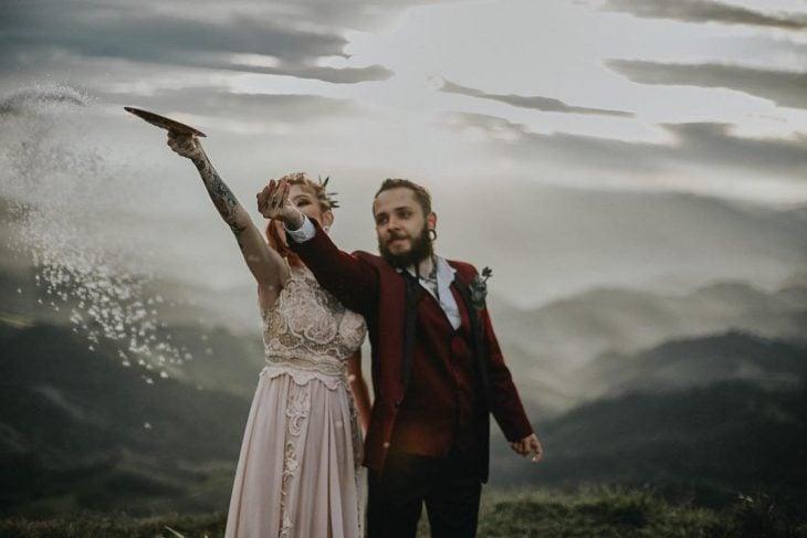 Pareja de novios celebra una boda nórdica al aire libre, novios vikingos arrojan sal al aire