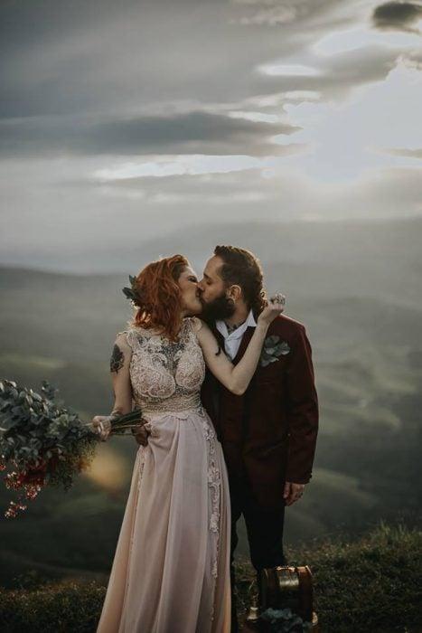Novios celebran una boda vikinga al aire libre, esposos besándose en una montaña