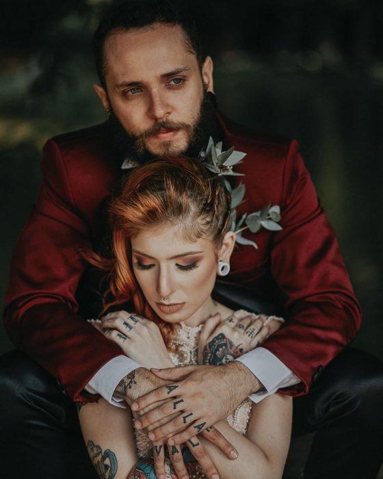 Pareja celebra boda vikinga, novio con traje rojo vino con negro abrazando a esposa con vestido de encaje y cabello pelirrojo
