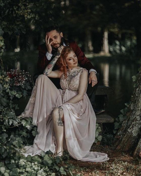 Sesión de fotos de recién casados en boda vikinga, esposos sentados en la naturaleza entre árboles