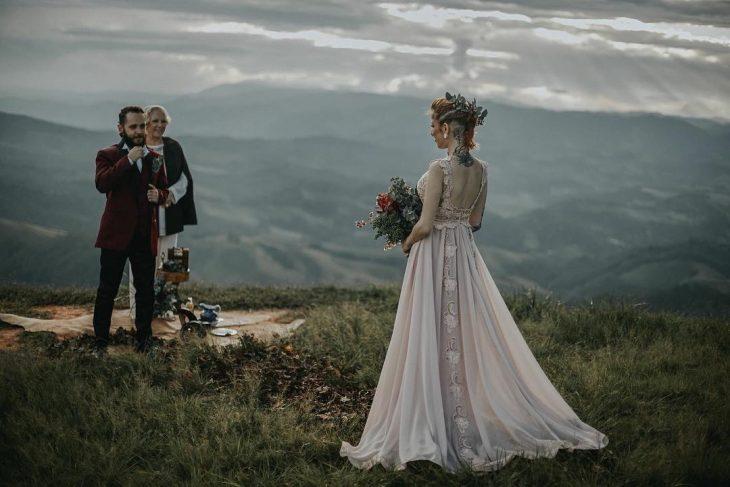 Pareja de novios con tatuajes celebra una boda vikinga al aire libre, esposa con vestido de encaje rosa y esposo con traje rojo