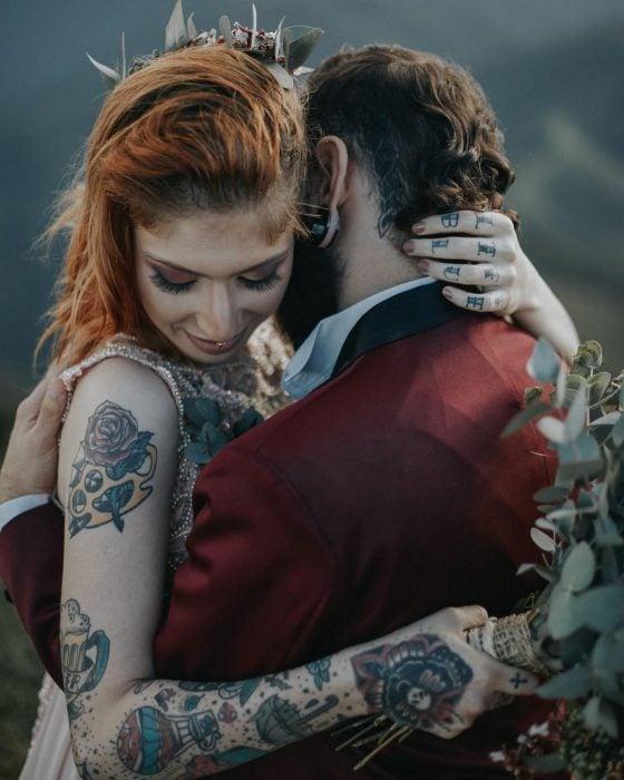 Novios se casan en boda vikinga, mujer pelirroja y con tatuajes abraza a novio con traje rojo vino