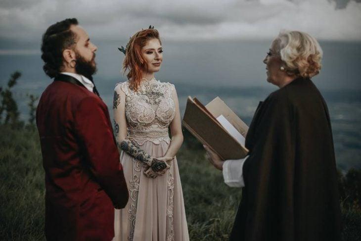 Pareja de prometidos se casa en boda nórdica, esposa con vestido de encaje rosa pálido y esposo con traje rojo vino, novios parados frente a jueza