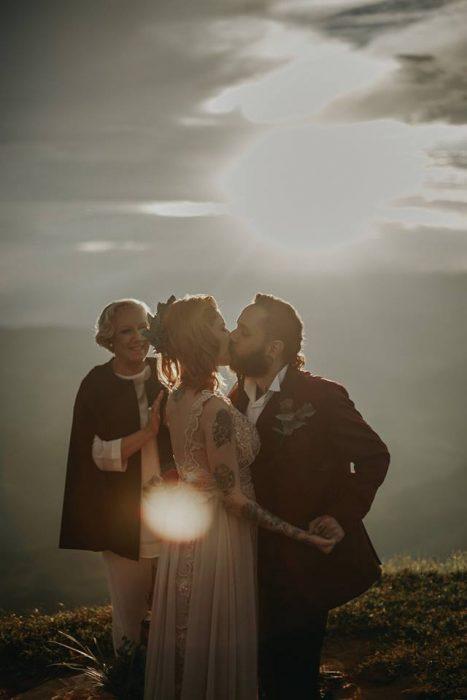 Boda vikinga en la montaña al aire libre, novio besando a novia al atardecer