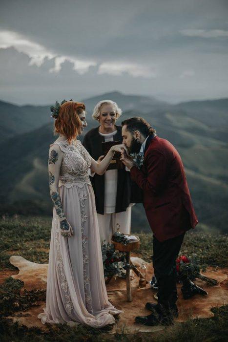 Pareja de novios con tatuajes celebra una boda nórdica al aire libre, novio con traje guinda besa la mano de su prometida con vestido largo vintage