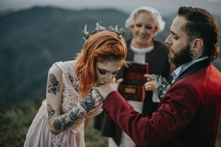 Pareja de novios con tatuajes celebra una boda nórdica al aire libre, novia de cabello rojo besa la mano de su novio con saco guinda