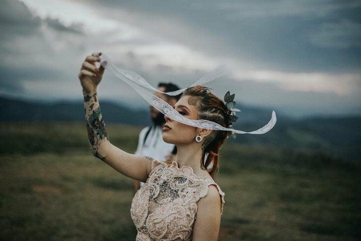 Pareja de novios celebra una boda nórdica al aire libre, mujer con tatuajes y expansiones con vestido de encaje con perlas sostiene listón de encaje blanco
