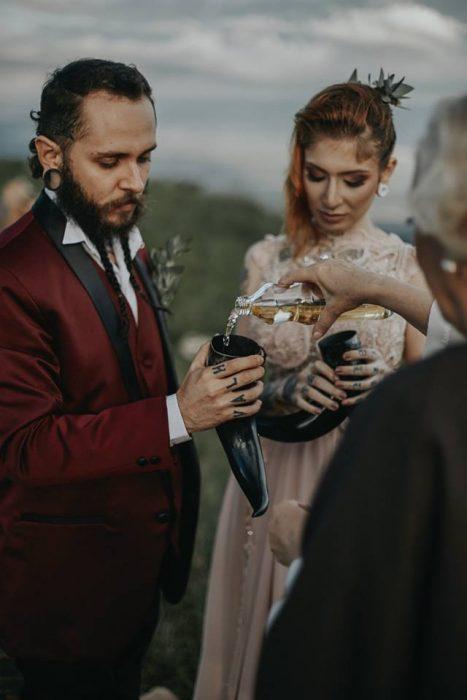 Pareja de novios celebra una boda nórdica al aire libre, novios con tatuajes y expansiones, beben hidromiel en cuernos vikingos