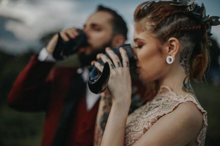 Pareja de novios celebra una boda nórdica al aire libre, novia con tatuajes en el cuello, brazos y manos, y expansiones y peinado de trenzas bebe hidromiel de cuerno vikingo
