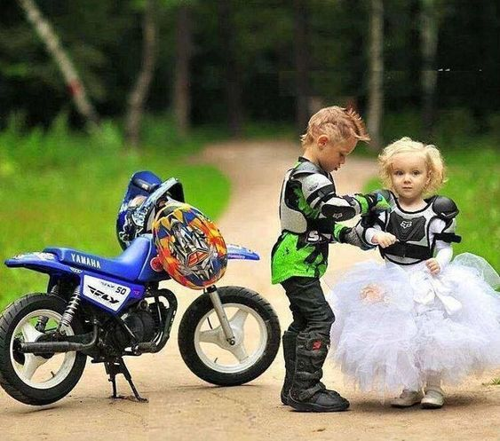 Children dressed as motorcyclists walking through a park while taking pictures as pages for a biker style wedding