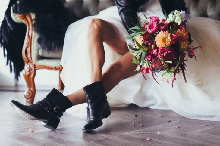 Bride wearing white fluffy dress, sitting on a step, showing off her black boots ideal for a biker style wedding