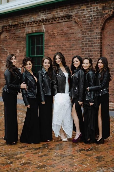 Bride surrounded by her bridesmaids wearing black with leather jackets for her biker style wedding