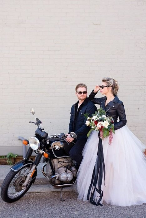 Newly-married wedding couple wearing black leather jackets, recharged on a sports bike ready to arrive at their biker-style wedding