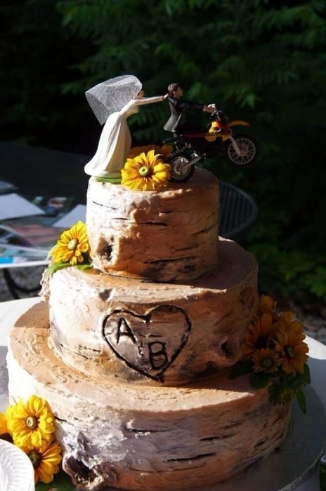 Three-tiered wedding cake with little bitumen decorated with sunflowers and a couple of motorcycle dolls, idea for a biker wedding
