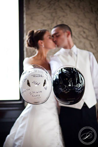 Couple of bride and groom holding motorcycle helmets with messages of congratulations for their biker style wedding