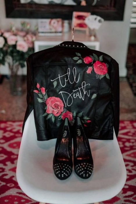 Black leather jacket hung on a chair, showing its embroidery on back with red roses, and a pair of black sneakers