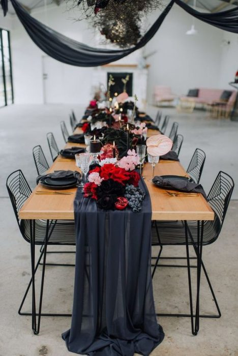 Tables decorated with red flowers, dark dishes, black tablecloths for a biker style wedding