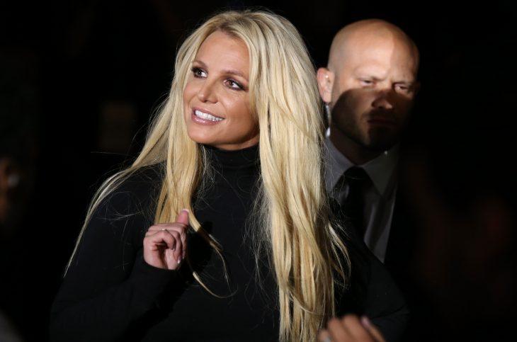 Britney Spears, chica caminando por la alfombra roja, llevando sueter negro, mirando hacia arriba, sonriendo, guiada por sus guardaespaldas