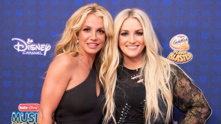 Chicas usando vestidos de gala color negro, abrazandose mutuamente, llevando cabello largo color rubio, sonriendo a la cámara, Britney y Jamie Lynn Spears