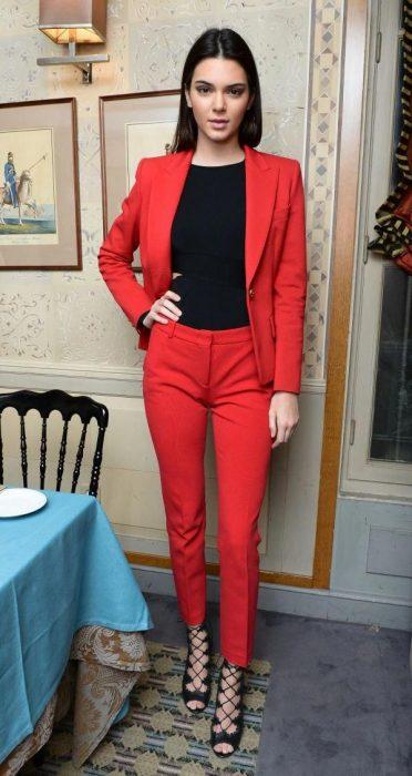 La modelo Kendall Jenner modelando un conjunto de pantalón y blazer rojo y zapatos altos de tacón.