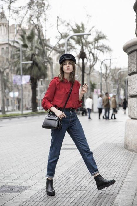 Chica modelando una blusa holgada roja, pantalón de mezclilla, bolso negro y sombrero negro