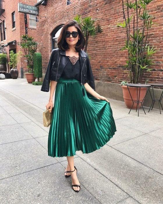 Chica caminando por la calle con un atuendo de falda verde holgada, una camiseta negra, gafas negras y sandalias de tacón