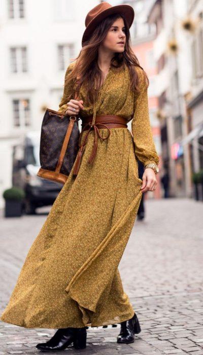 Chica caminando por la calle con un maxivestido color mostaza, botines negros, sombrero café y bolsa de mano