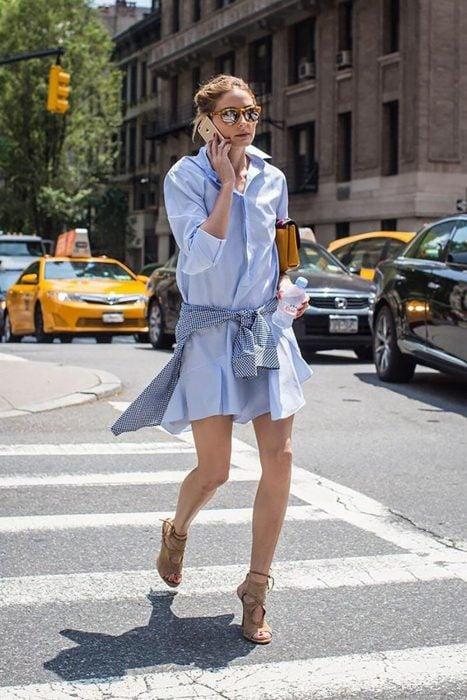 Chica caminando por la calle mientras habla por su celular, con vestido de camisa azul, camisa de cuadros amarrada a su cintura y gafas reflectantes