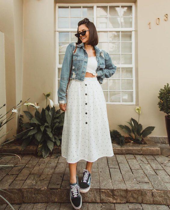 Chica modelando una falda larga blanca de lunares negros, un top blanco, chamarra de mezclilla y unos tenis negros con adornos en blanco y gafas oscuras