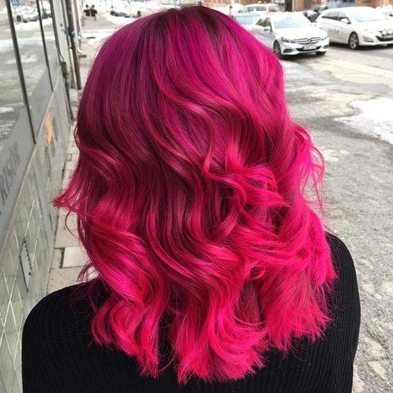 Chica con cabello midi, teñido en bold pink, volteada de espaldas, usando sudadera negra