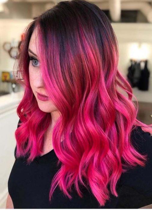 Chica dentro de una habitación, sentada de perfil, llevando blusa oscura, cubriendo la mitad de su rostro con su cabello color Bold Pink