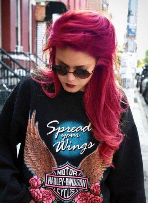 Chica con cabello bold pink, sudadera negra, estampado azul, gafas oscuras, caminando con la cabeza hacia abajo por las calles