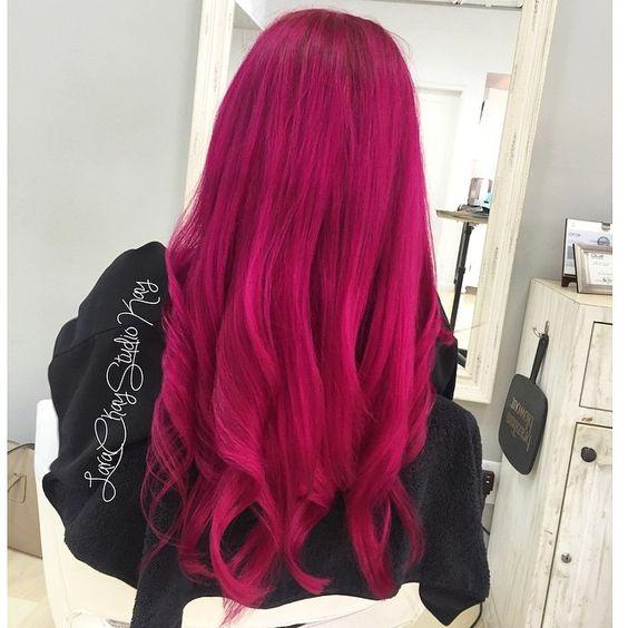 Chica dentro de una habitación con muebles blancos, girada de espaldas, usando chaqueta negra, mostrando su cabellera larga teñida en color bold pink