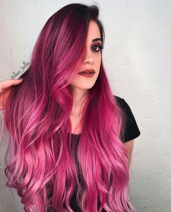 Chica con cabello largo, teñido en color bold pink, con degradado en rosa pastel, usando camisa negra, acariciando su cabello con su mano derecha
