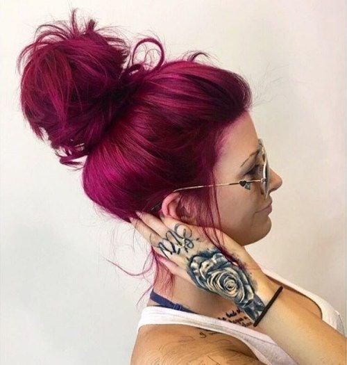 chica con tatuaje en la mano, tocando su nuca, volteada d eperfil para mostrar si peinado bun y su cabello teñido en color bold pink