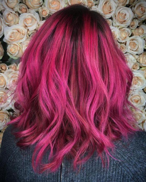Chica voletada de espaldas, mirando a una pared decorada con flores, mostrando su cabello corto teñido de color bold pink