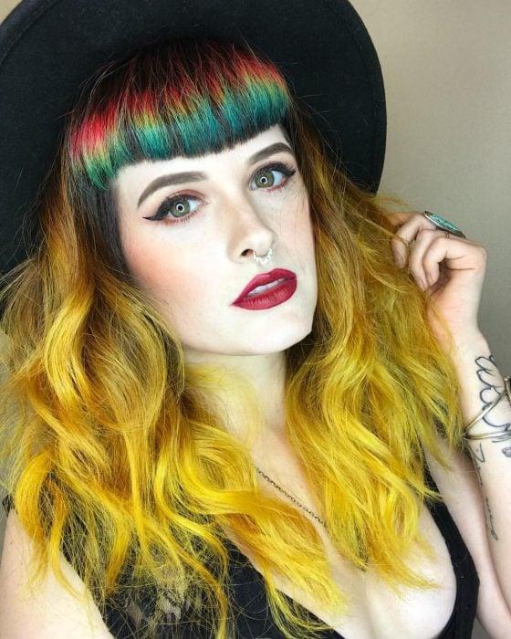 Chica con sombrero negro y cabello largo y ondulado color amarillo con fleco de colores rojo, amarillo y verde