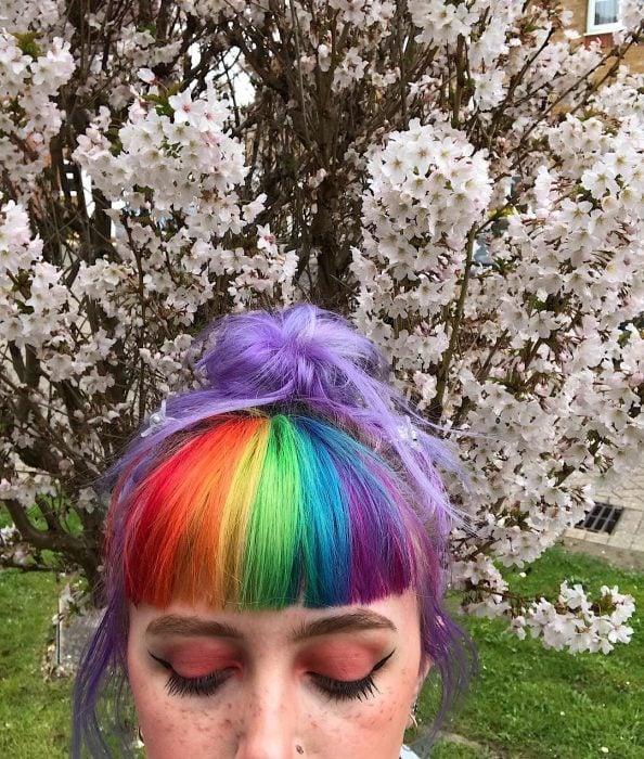 Chica con pecas y cavello lila con fleco de colores rojo, anaranjado, amarillo, verde, azul y morado frente a un árbol de flores blancas