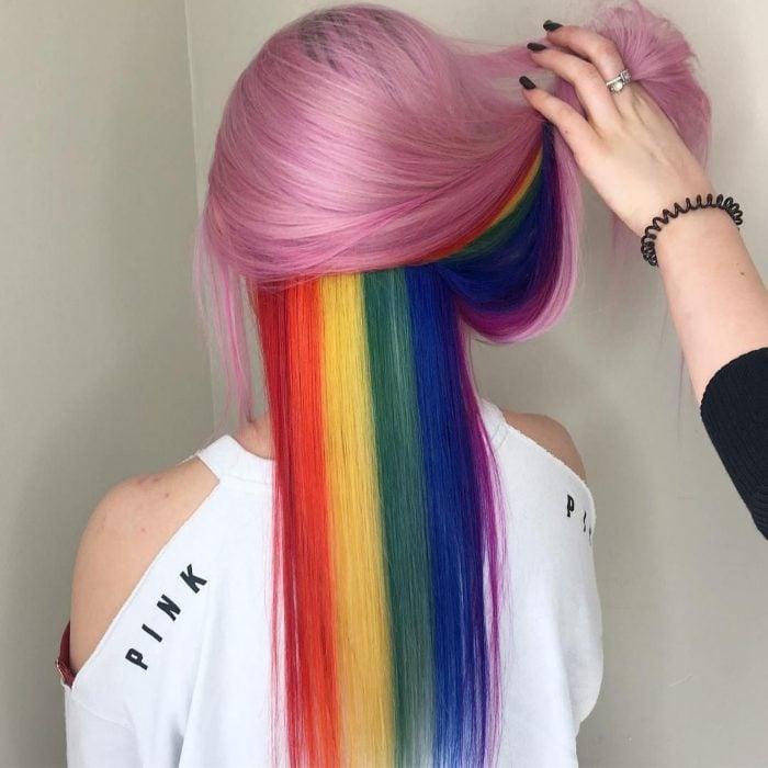 Chica de cabello largo y lacio color rosa con colores escondidos, rojo, anaranjado, amarillo, verde, azul y morado